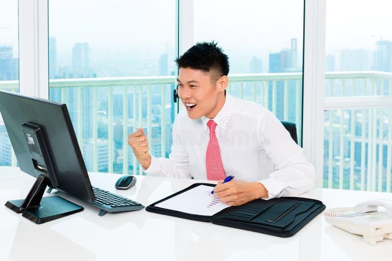 Mediatore asiatico che vende alla borsa valori in ufficio che realizza profitto immagine stock libera da diritti
