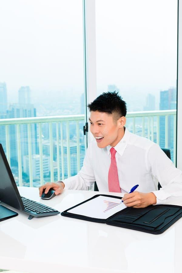 Mediatore asiatico che vende alla borsa valori in ufficio che realizza profitto fotografia stock libera da diritti