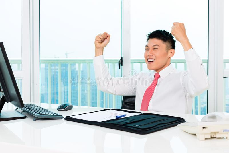 Mediatore asiatico che vende nell'ufficio che realizza profitto fotografia stock