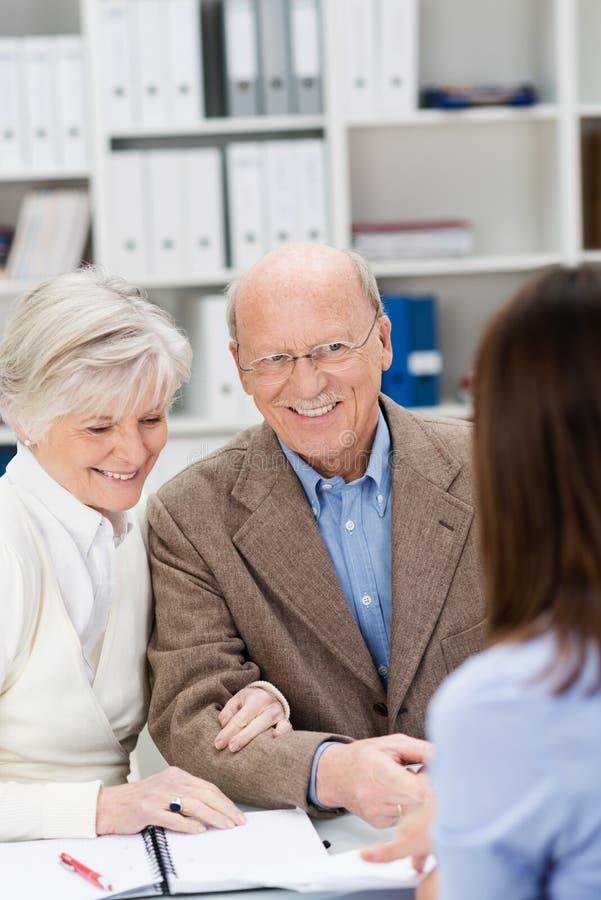 Mediatore che chiacchiera ad una coppia senior sorridente fotografie stock