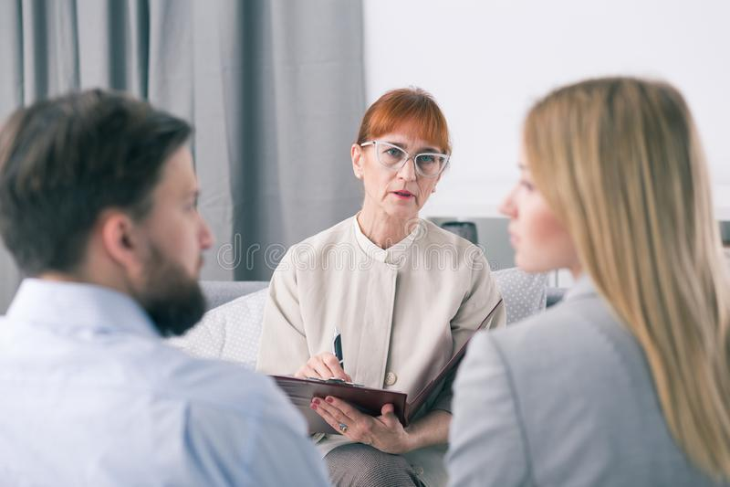 Mediatore che parla con coppia durante la sessione immagine stock