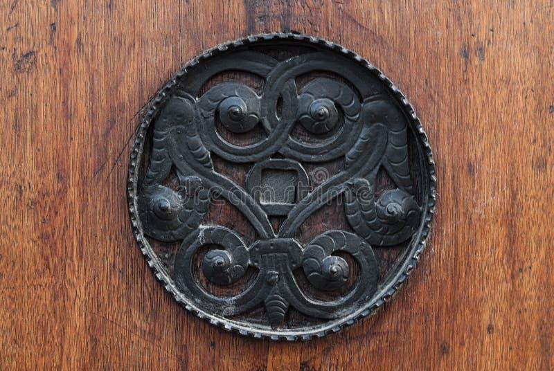 Mediaval Bronze doorknob. Sigil on old wooden door stock image