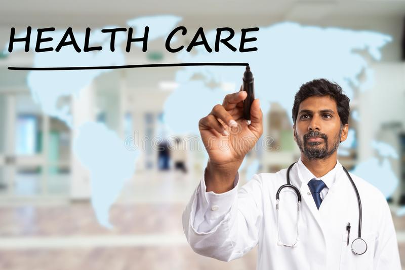 Medic drawing line under health care text. Indian medic man drawing black marker line under health care text on transparent display with blue world map as stock photo