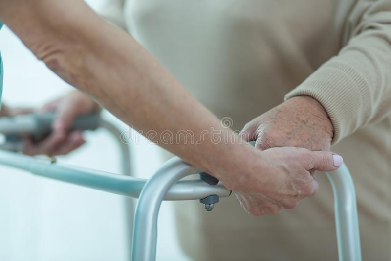 Medic helping patient with zimmer royalty free stock image