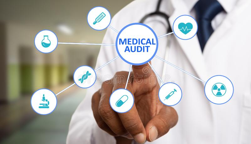 Medic touching medical audit text on display. Indian male medic touching medical audit text circle button on close-up futuristic display with healthcare symbols royalty free stock images