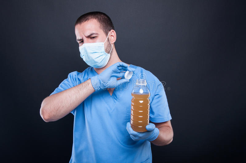 Medic wearing face mask holding bad smelling water. Like water pollution concept on black background stock images