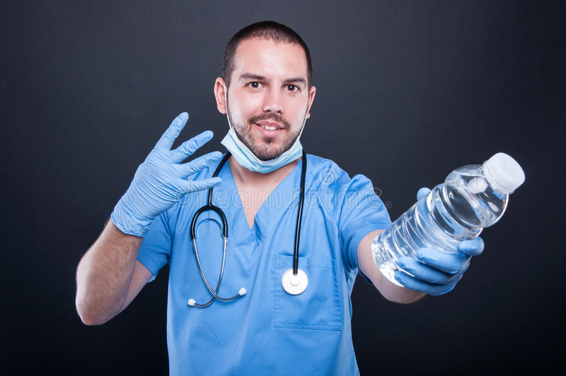 Medic wearing scrubs showing water and number four royalty free stock photos