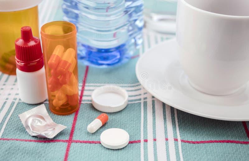 Medicación durante el desayuno, cápsulas al lado de un vaso de agua, imagen conceptual fotos de archivo