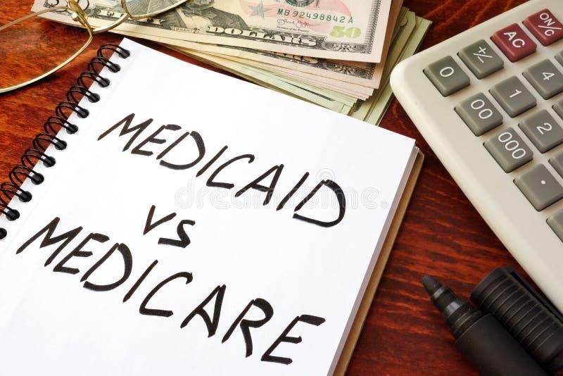 Medicaid versus Gezondheidszorg voor bejaarden in een nota wordt geschreven die stock foto