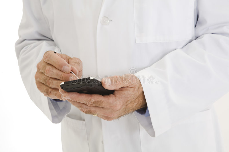 Caucasian doctor wearing a white lab coat using PDA royalty free stock images