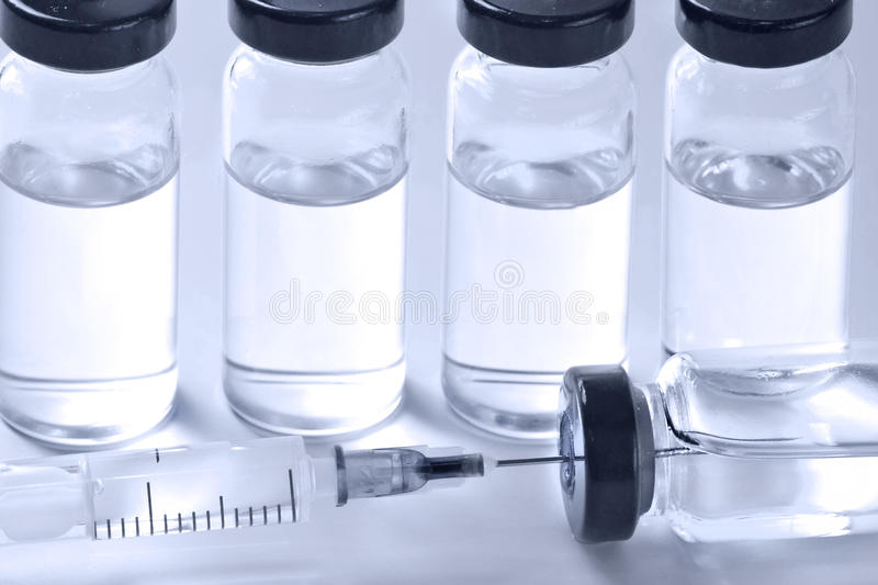 Medical ampoules with vaccine and syringe on white background royalty free stock photo