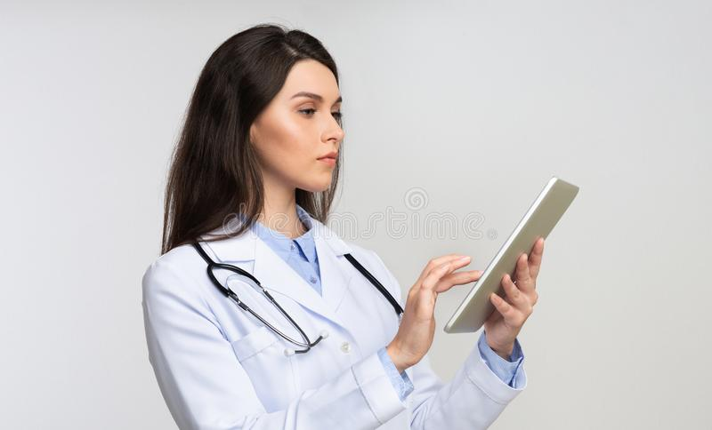 Serious Lady Doctor Using Digital Tablet Standing Over White Background stock image