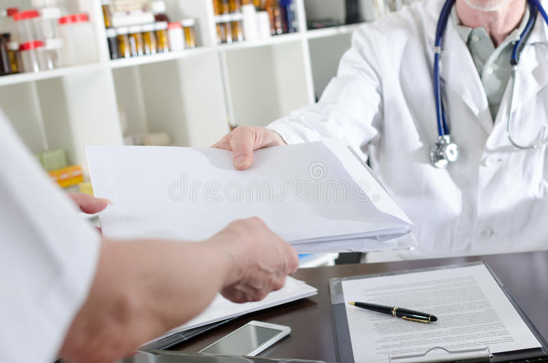 Medical assistant handing folders to the doctor. In medical office royalty free stock photos