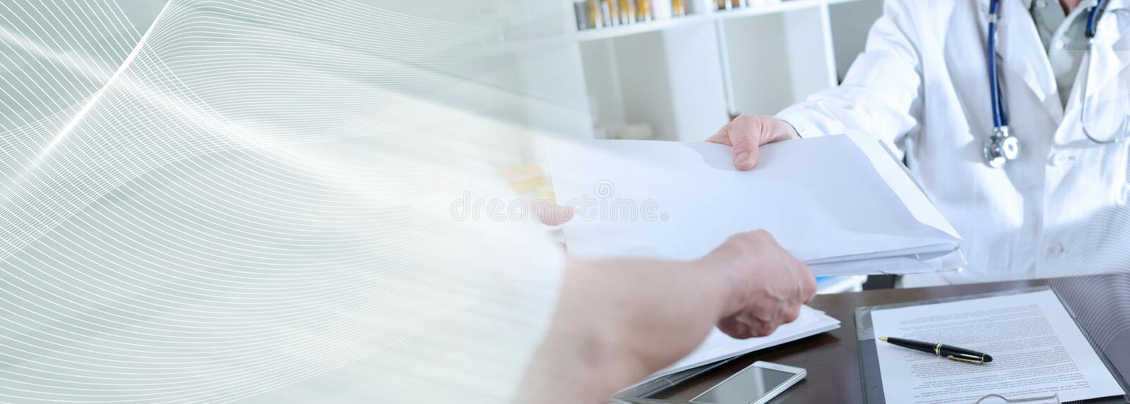 Medical assistant handing folders to the doctor; panoramic banner stock photo