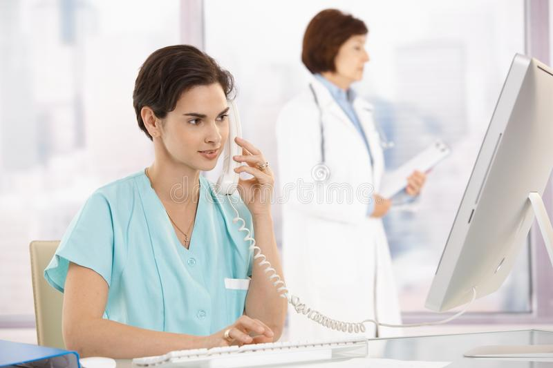 Medical assistant on phone, using computer. Medical assistant sitting at desk, talking on landline phone, using computer, doctor in background stock images