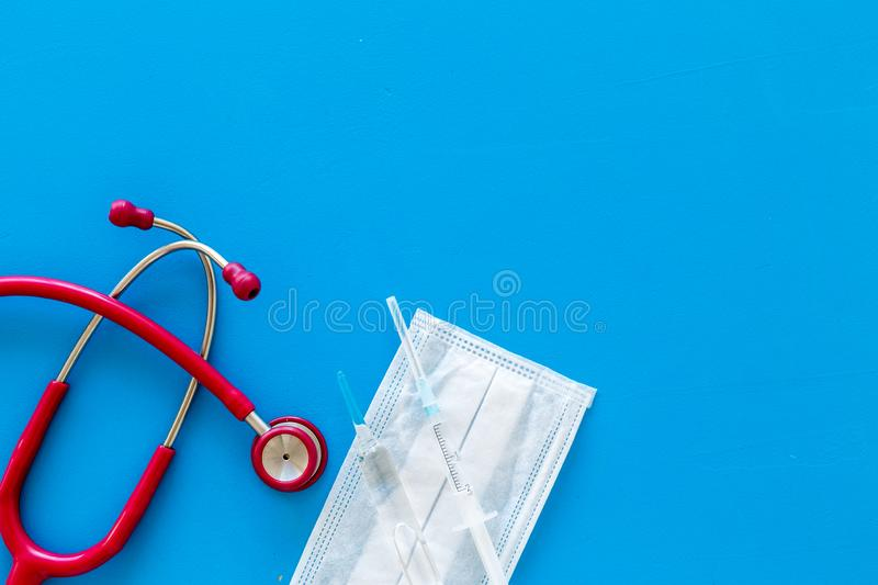 Medical background with face mask, stethoscope, vaccine on blue background top view copy space. Medical background with face mask, stethoscope, vaccine on blue royalty free stock image