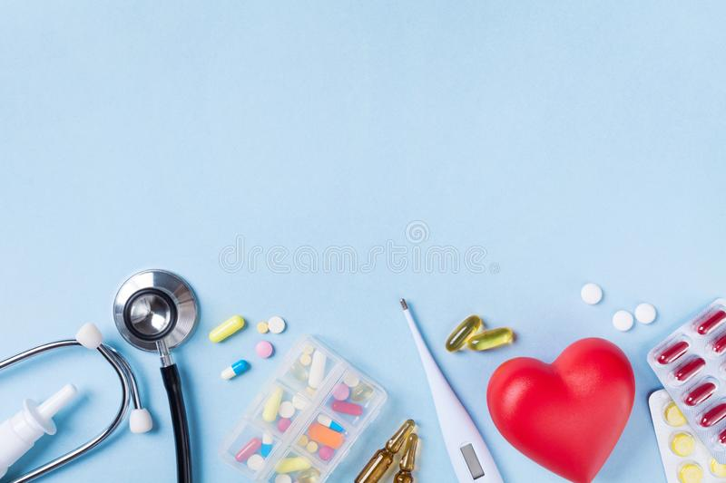 Medical background from pharmaceutical tablets and pills, stethoscope, heart and thermometer top view. Healthcare and medicine. Concept stock photos