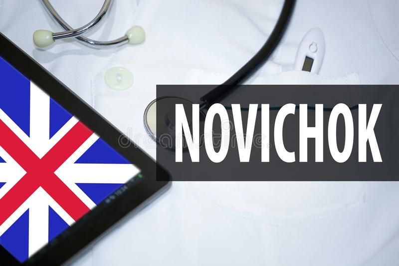 Medical bathrobe, tablet with English flag and inscription with Russian in Latin transcription - `Novichok`. News concept.  royalty free stock image
