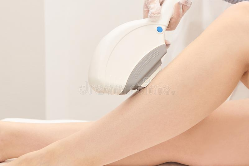 Medical beauty laser cosmeology procedure. Young female at salon. Professional doctor. Woman skincare technology. Hair removal.  royalty free stock image