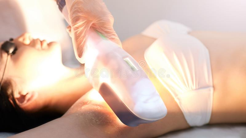 Medical beauty laser cosmeology procedure. Young female at salon. Professional doctor. Woman skincare technology. Hair removal.  royalty free stock photos