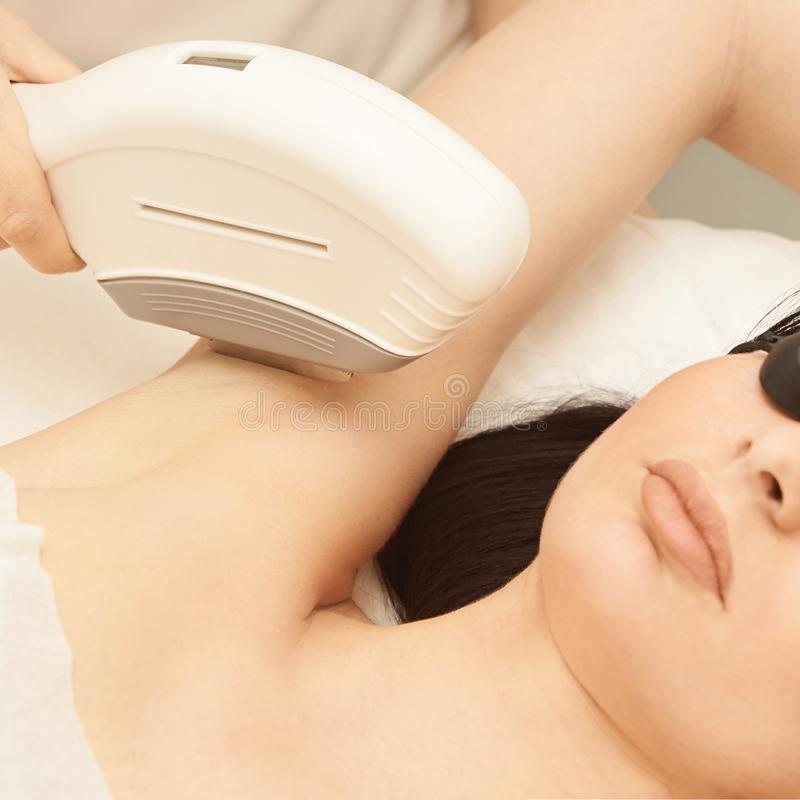 Medical beauty laser cosmeology procedure. Young female at salon. Professional doctor. Woman skincare technology. Hair removal royalty free stock photos