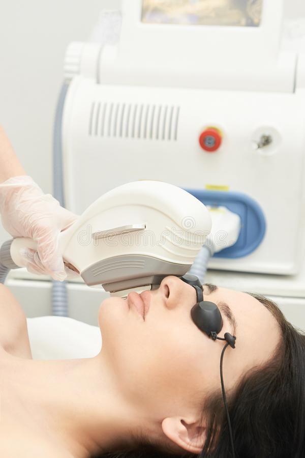 Medical beauty laser cosmeology procedure. Young female at salon. Professional doctor. Woman technology. Hair removal royalty free stock photography