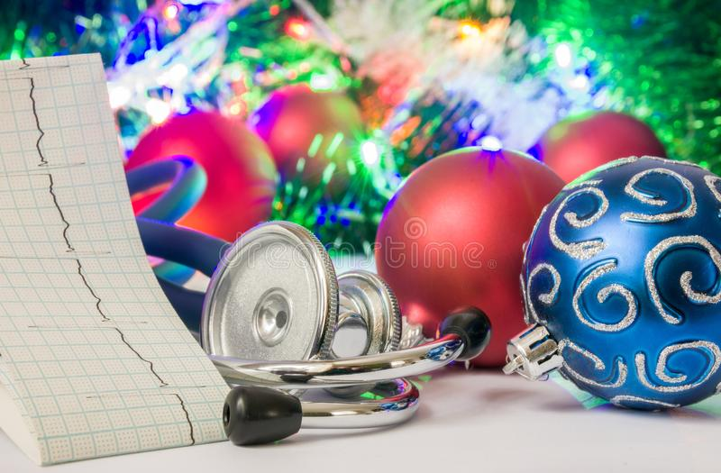 Medical cardiology Christmas and New Year photo - stethoscope and electrocardiogram tape are located near balls for Christmas tree stock photo