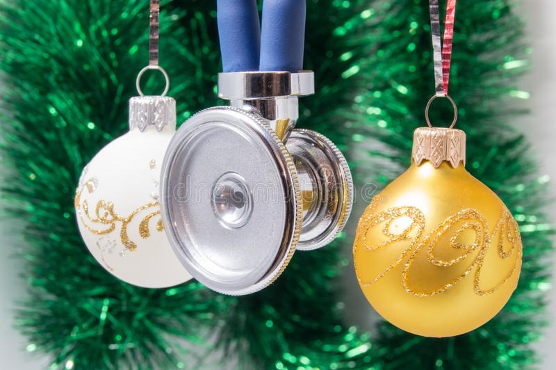 Medical Christmas and New Year. Stethoscope surrounded by white and gold christmas tree balls with blurred christmas decoration on stock image