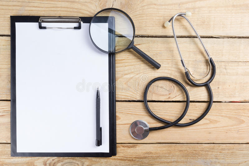 Medical clipboard and stethoscope, magnifying glass, black pen on wooden desk background. Top view. Workplace of a doctor. royalty free stock image
