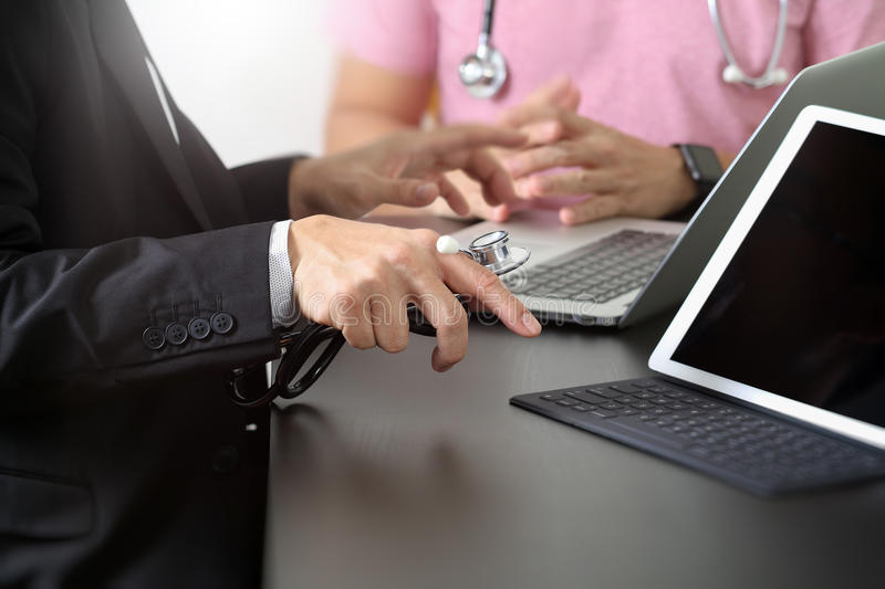Medical co working concept,Doctor working with smart phone and d. Igital tablet and laptop computer to meeting his team in modern office at hospital royalty free stock image
