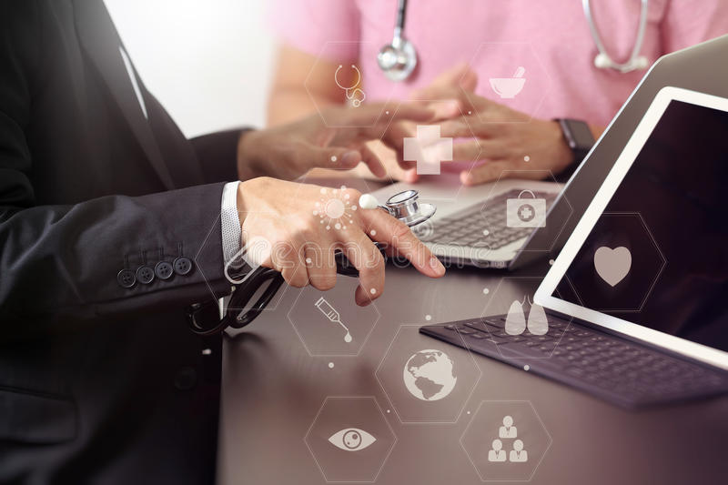 Medical co working concept, Doctor working with smart phone and d. Igital tablet and laptop computer to meeting his team in modern office at hospital with royalty free stock image