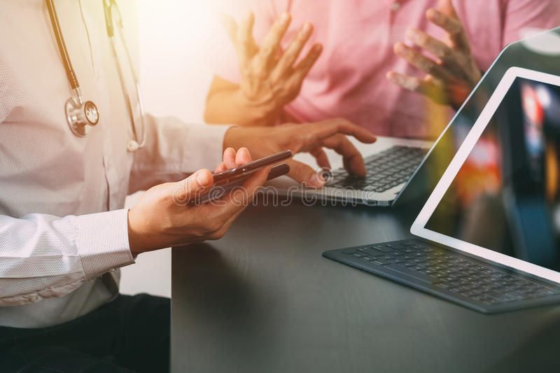 Medical co working concept,Doctor working with smart phone and d. Igital tablet and laptop computer to meeting his team in modern office at hospital royalty free stock images