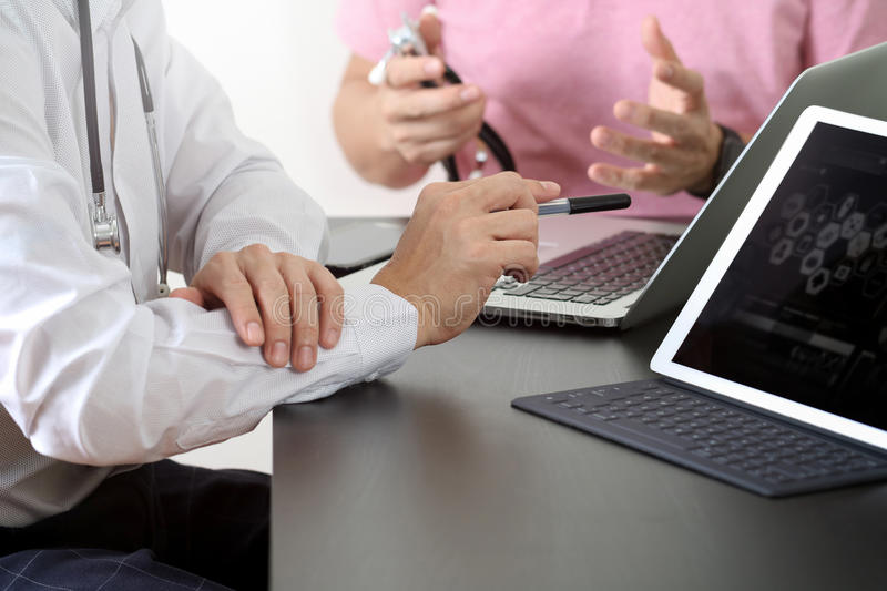 Medical co working concept,Doctor working with smart phone and d. Igital tablet and laptop computer to meeting his team in modern office at hospital stock photo