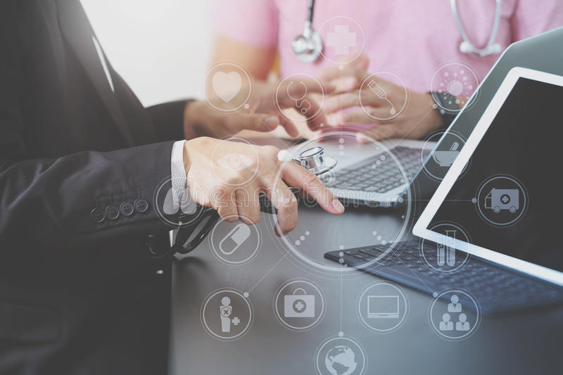 Medical co working concept,Doctor working with smart phone and d. Igital tablet and laptop computer to meeting his team in modern office at hospital with virtual royalty free stock images