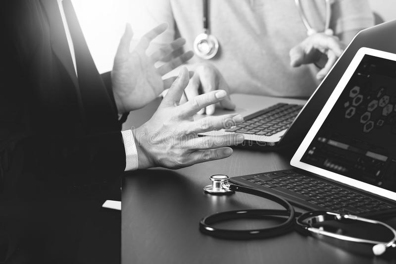 Medical co working concept,Doctor working with smart phone and d. Igital tablet and laptop computer to meeting his team in modern office at hospital,black and royalty free stock photos