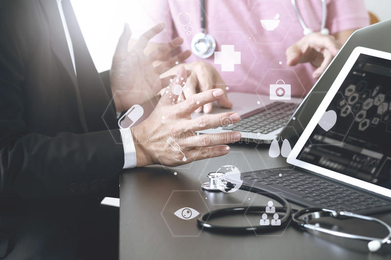 Medical co working concept,Doctor working with smart phone and d. Igital tablet and laptop computer to meeting his team in modern office at hospital with virtual royalty free stock image