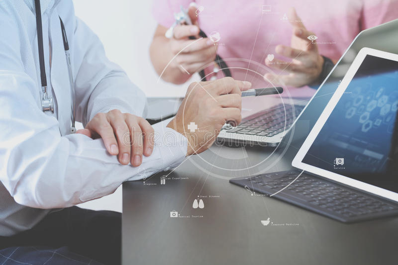 Medical co working concept,Doctor working with smart phone and d. Igital tablet and laptop computer to meeting his team in modern office at hospital with virtual stock photo
