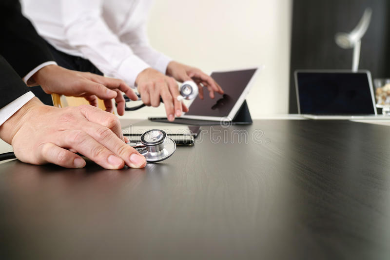 Medical co working concept,Doctor working with smart phone and d. Igital tablet and laptop computer to meeting his team in modern office at hospital royalty free stock photography