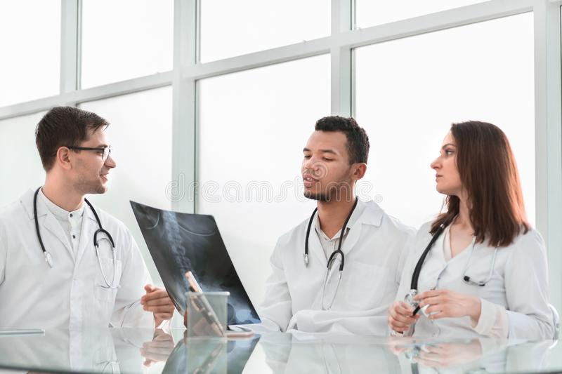 Medical colleagues discuss x-ray, sitting at the office table. The concept of health stock image