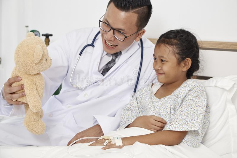 Little girl and doctor in hospital stock images