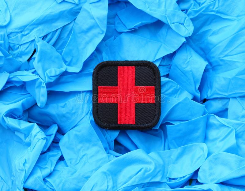 Medical Cross Patch On Blue Hospital Gloves royalty free stock image