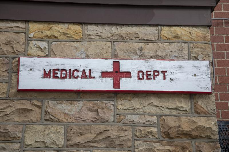 Medical department wooden sign. Wooden sign with medical department on brick wall exterior of old prison stock images