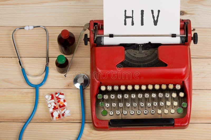 Medical diagnosis - doctor workplace with blue stethoscope, pills, red typewriter with text HIV. Prescription medicine or medical diagnosis - doctor workplace royalty free stock image