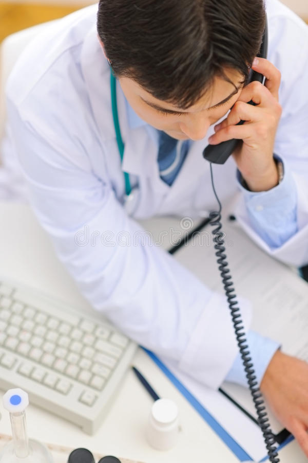Medical doctor dialing phone number. Upper view stock photography