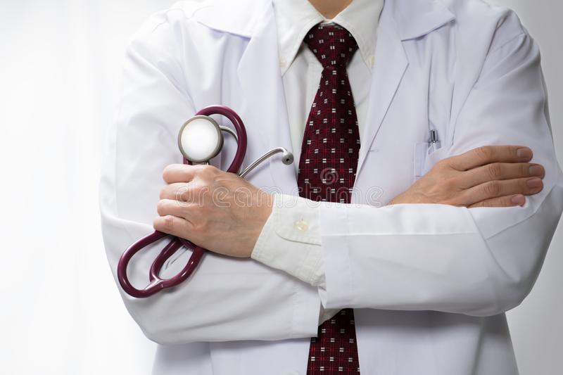 Medical doctor holding a stethoscope with arms crossed and copy space stock photos