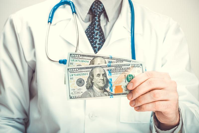 Medical doctor holding USA dollars in his hands - close up studio shot stock photos