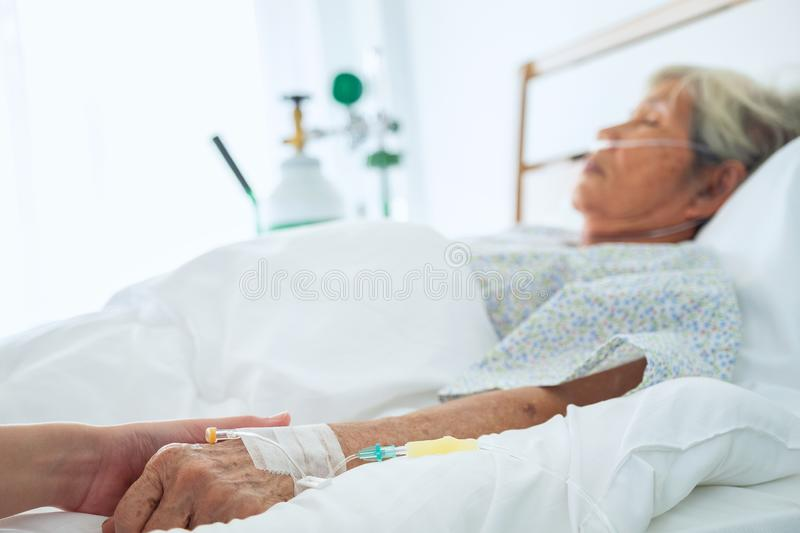 Medical doctor holing senior patient`s hands and comforting her,. Hand of man touching senior woman in clinic, care for the elderly concept royalty free stock images