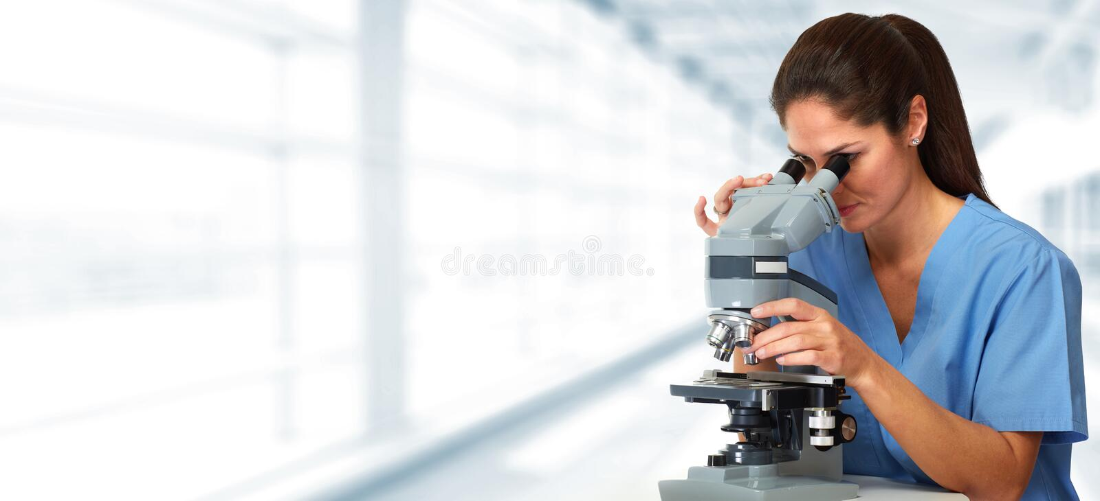 Medical doctor with microscope. Scientific doctor woman with microscope in medical laboratory royalty free stock image