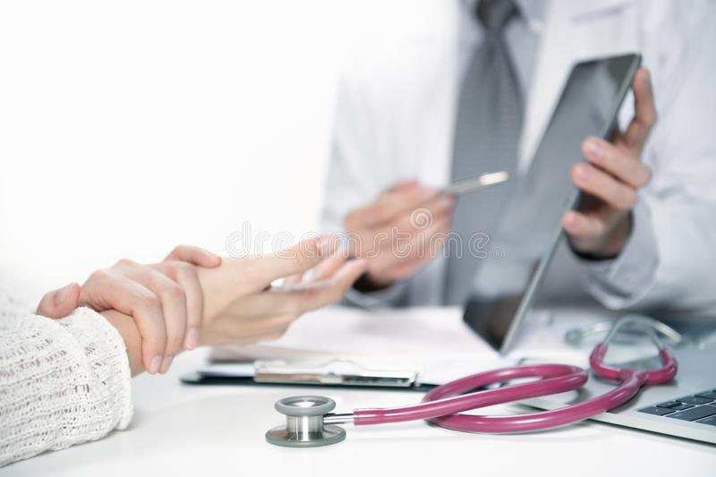 Medical doctor and patient discussing and consulting in hospital examination room stock image