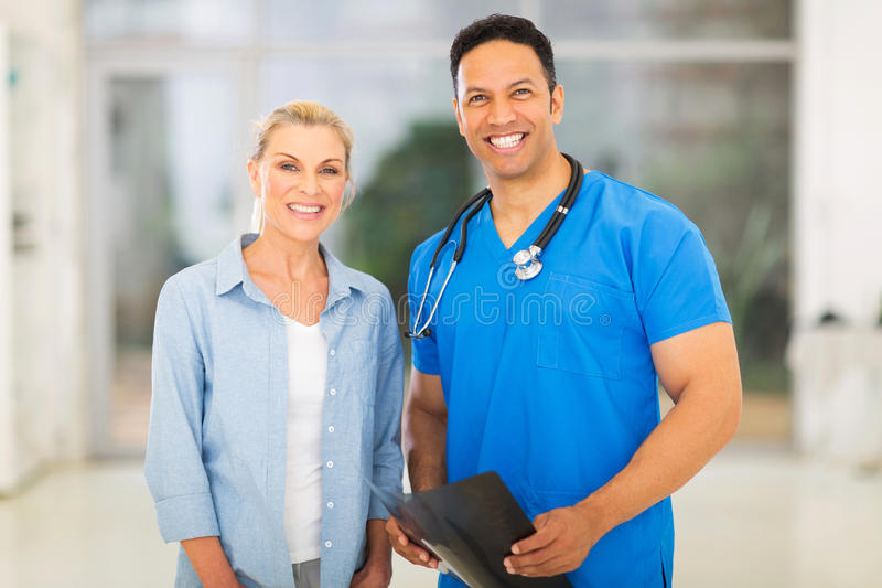 Medical doctor patient. Portrait of friendly medical doctor standing with senior patient royalty free stock photos